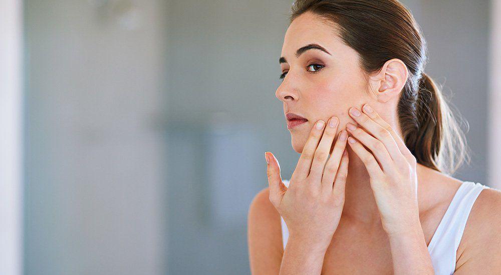 mulher adulta olhando rosto acne espelho - Acne adulta: descubra o que causa e como evitar!