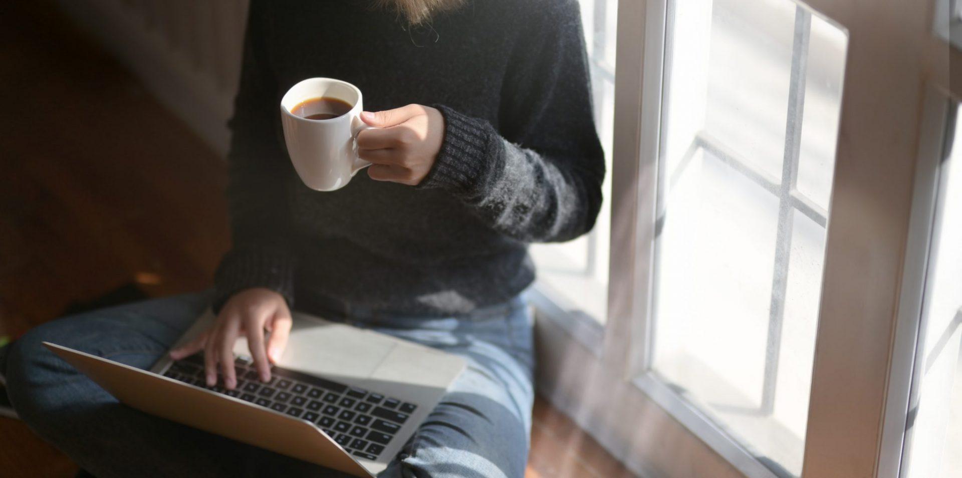womanusinglaptopwhileholdingacupofcoffee3759083 1 scaled - Por que devo ser contratado? Dicas para se tornar mais atraente para as empresas