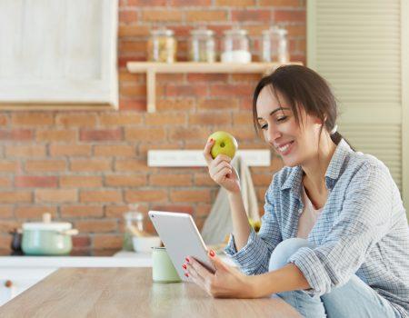 7 dicas para fortalecer a imunidade - Moça trabalhando com um tablet e comendo uma maçã