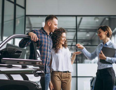 Guia de como comprar um carro semi novo - Casal comprando um carro novo da concessionária